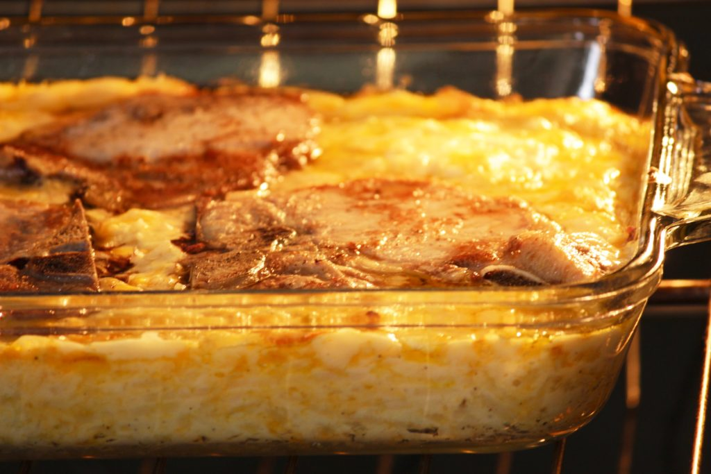 Cheesy pork chop casserole cooking in the oven with the oven light on