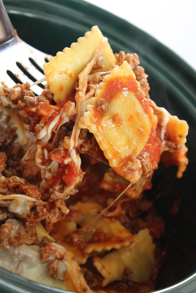ravioli casserole on a spoon over the crockpot