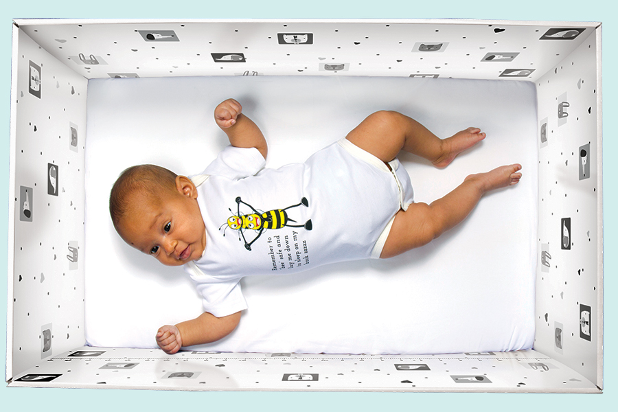 Baby laying in a baby box like the ones they use in Finland