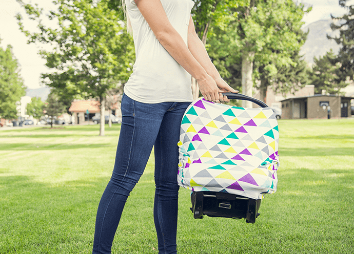 Woman carrying baby seat with a patterned carseat cover.