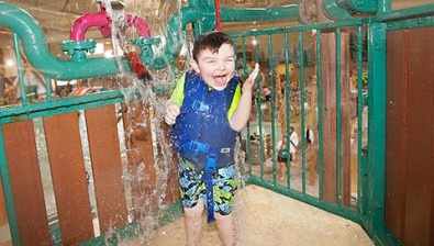 Child getting water splashed on his head at the Great Wolf Lodge Kansas City location