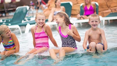 Kids sitting on the side of the pool at the Great Wolf Lodge Traverse City Michigan Location