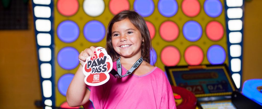 Girl wearing pink shirt showing Great Wolf Lodge Paw Pass