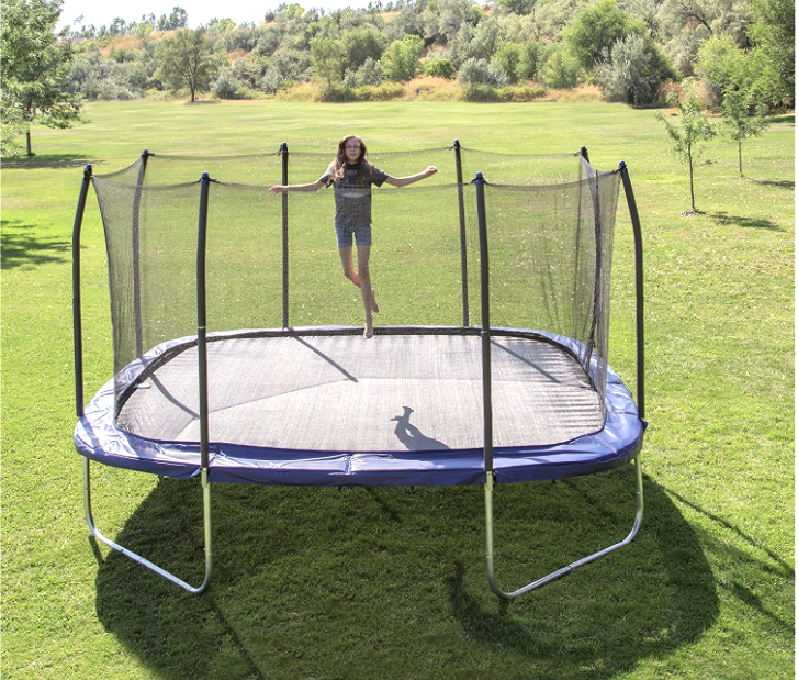 girl jumping on a rectangle trampoline in the sunshine