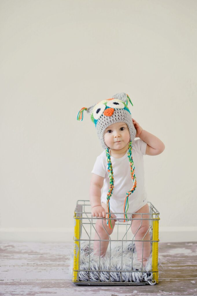baby with hat in onesie and diaper