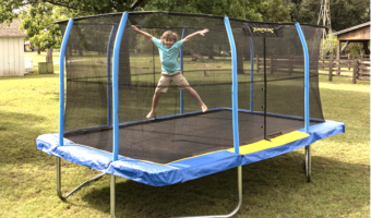 Boy in green shirt jumping on a rectangle trampoline